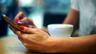 Young woman using smartphone and drinking coffee in cafe, focus on hands