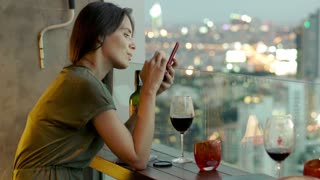 Young woman using smartphone sitting in cafe in city