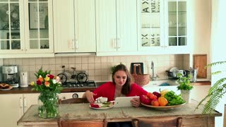 Young woman using tablet while eating breakfast by table in the kitchen