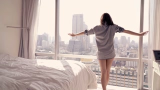 Young woman waking up from sleep and admire splendid city view from the window, 4K