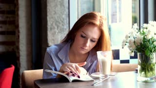 Young woman with red hair reading book in cafe