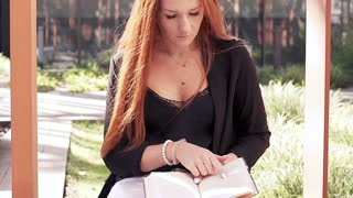 Young woman with red hair reading book in the city