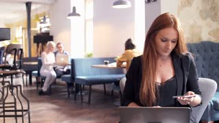 Young woman with red hair working on laptop and smartphone by table in cafe