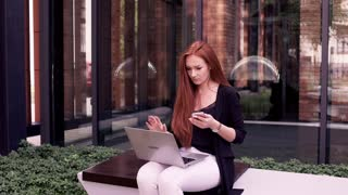 Young woman with red hair working on laptop and smartphone on the bench in the city