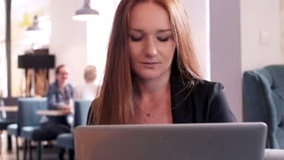 Young woman with red hair working on laptop in cafe