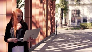 Young woman with red hair working on laptop in the city