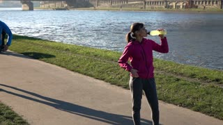 Woman drinking water after workout, man jogging in  city street close to the river, super slow motion, 240fps