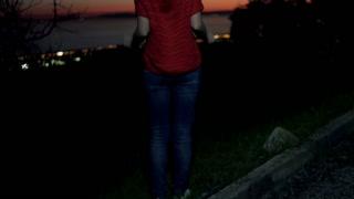 Woman enjoying beautiful sunset standing on the rock