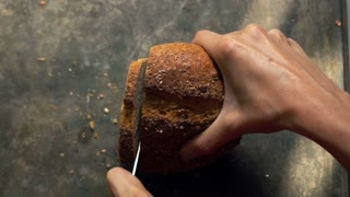 Woman hand slicing bread, super slow motion