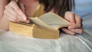 Woman hand turning page of the book  lying on bed