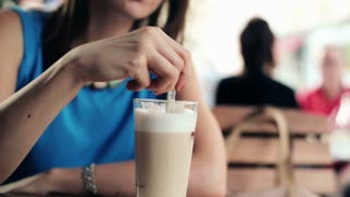 Woman hands mixing coffee in the city cafe
