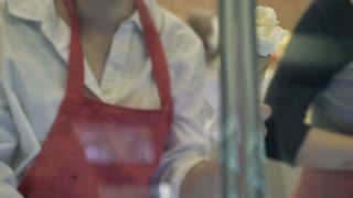 Woman hands put ice scream on waffle in the pastry shop