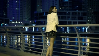 Woman looking on the river in modern city during night, 4K