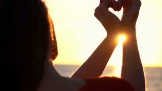 Woman making heart symbol with her hands during sunset on beach, super slow motion