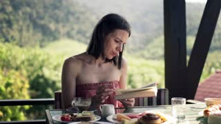 Woman reading book book and drinking during breakfast on  the terrace