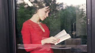 Woman reading book standing by the window