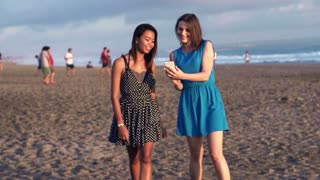 Woman showing something on smartphone to her friend on the beach, super slow motion, shot at 240fps