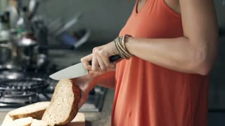 Woman slicing bread in the kitchen, 4K