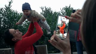 Woman taking photo of mother with small baby at home, super slow motion