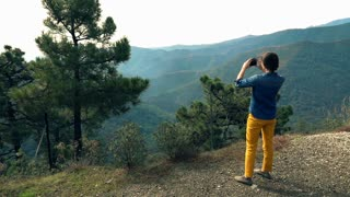 Woman taking photo with cellphone on the splendid hills view, super slow motion