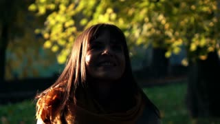 Woman throwing golden leaves in autumn park, slow motion, shot at 240fps