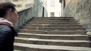 Woman walking up on ancient stairs in italy