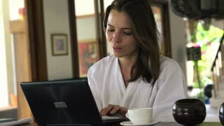 Woman with laptop having coffee break by table at home