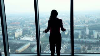Silhouette of successful woman raising arms, power symbol, in the office, super slow motion