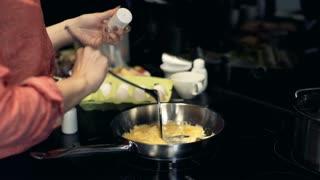 Woman hands mixing scrambled eggs on frying pan