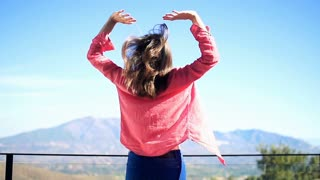 Young, happy woman turning around in the morning on terrace, super slow motion
