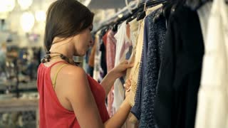 Young, attractive woman checking clothes at shop, 4K