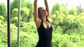 Young attractive woman doing yoga pose at terrace with beautiful view, slow motion, shot at 240fps