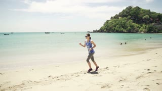 Young attractive woman jogging on the beach, shot at 240fps