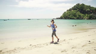 Young attractive woman jogging on the beach