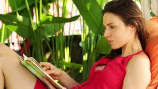 Young attractive woman reading book in the garden