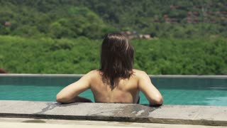 Young attractive woman relaxing on swimming pool, shot at 240fps