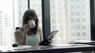 Young, beautiful businesswoman reading news on tablet computer while sitting by desk in office