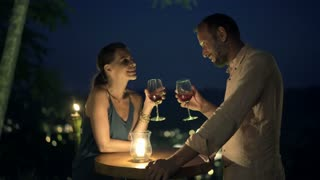 Young, beautiful couple talking and drinking wine in bar in the evening
