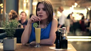 Young, beautiful woman drink tasty cocktail at the restaurant