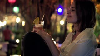 Young beautiful woman drinking cocktail sitting in trendy outdoors cafe, at night
