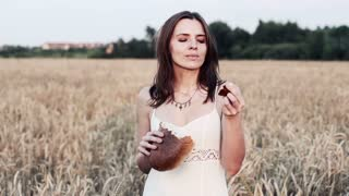 young beautiful woman eating bread among field