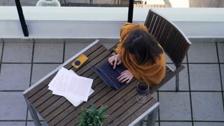 Young, beautiful woman finish working on laptop and drinking red wine sitting by table at terrace, top view