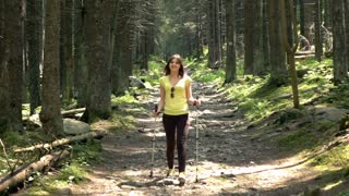 Young, beautiful woman hiking in the forest, super slow motion