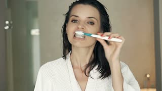 Young beautiful woman in bathrobe brushing her teeth in bathroom