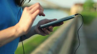 Young, beautiful woman listening to the music on smartphone by the river