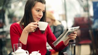 young beautiful woman reading newspaper and drinking tea in the cafe