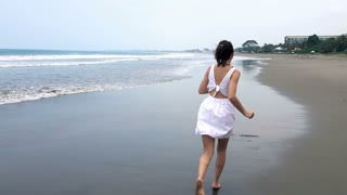 Young, beautiful woman running on beach, super slow motion