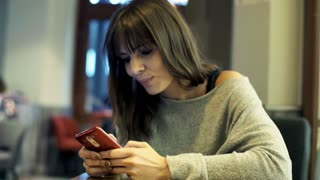Young beautiful woman sitting with smartphone in cafe