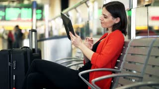 Young, beautiful woman sitting with tablet at train station