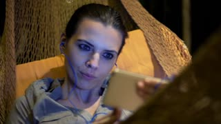 Young beautiful woman watching funny movie on smartphone while lying on hammock